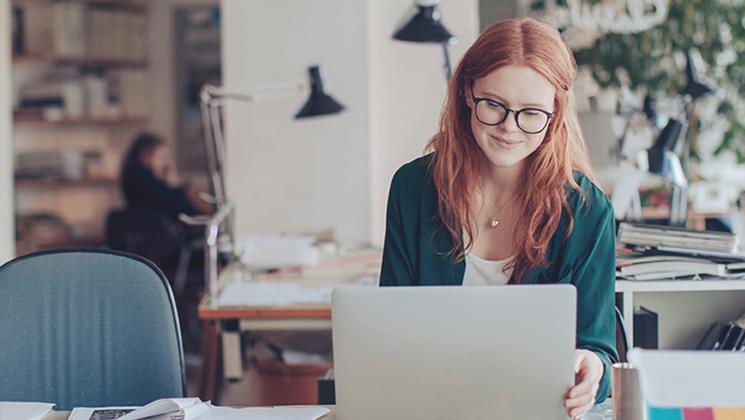 Rødhåret kvinde der sidder og arbejder på sin computer