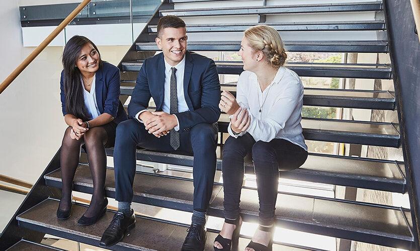 Tre medarbejdere der sidder på en trappe og snakker