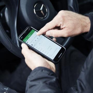Closeup af håndværker der bruger Ordrestyrings app'en i sin bil