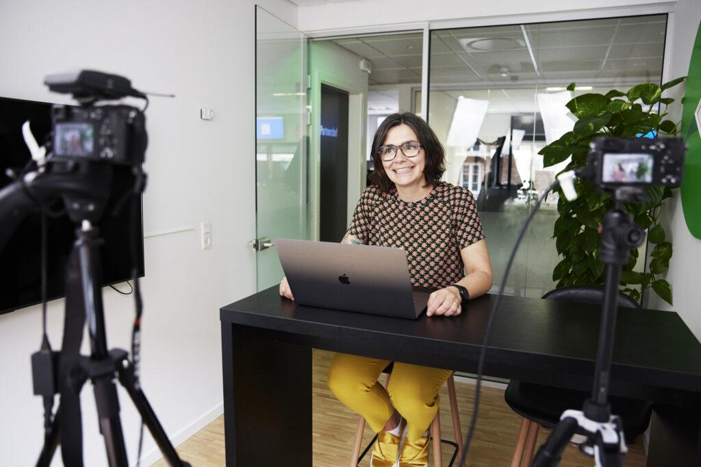 Marianne Askholm der sidder smilende ved et højt sort bord med et kamera foran hende og filmer Ordrestyring hjælpevideoer